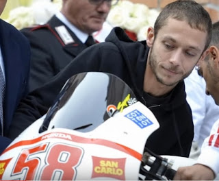 Valentino Rossi pictured at Simoncelli's funeral with one of the two motorcycles placed either side of the coffin