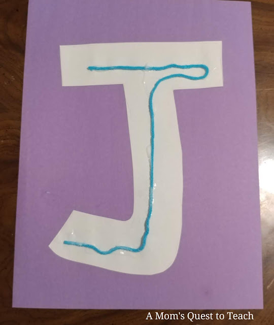 Letter J made of construction paper glued onto purple construction paper with yarn glued on it