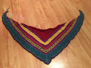 A multicoloured shawl with mosaic knitting bands of colourwork and a picot edge.