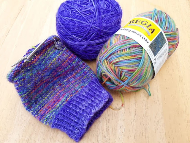 A partially-knitted sock with two balls of yarn.  One ball is purple and the other is multi-coloured