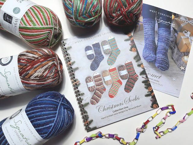 A flatlay of five balls of yarn in the WYS Christmas 2020 colours, a pattern book in the centre and a single pattern to the right.  There is also a small coloured paper chain at the bottom of the picture