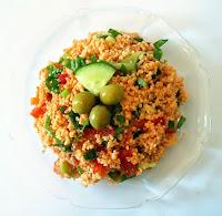 Üzerinde yeşil zeytin ve salatalık dilimi olan bir tabak kısırın üstten görünümü