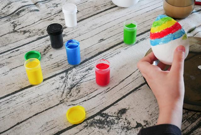 Dziecko maluje pisankę farbami plakatowymi. Nanoci kolejne warstwy w innym kolorze.
