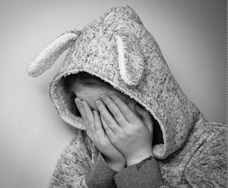 A picture of a child wearing a onesie suit with rabbit ears, with their hands over their eyes, as if they are sad.