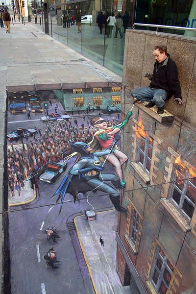Yüksek bir binanın penceresinde mahsur kalmış bir adamı kurtaran Robin ve Batman'i gösteren kaldırım sanatı resmi