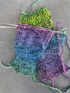 A pair of fingerless mittens, knit with yarns held double -- one yarn is black laceweight and one is a fingering-weight rainbow gradient.  One mitten is laying flat with a slipped-stitch pattern on the palm, one mitten is on double-pointed needles and laying palm down, showing stocking stitch and a small eyelet motif.