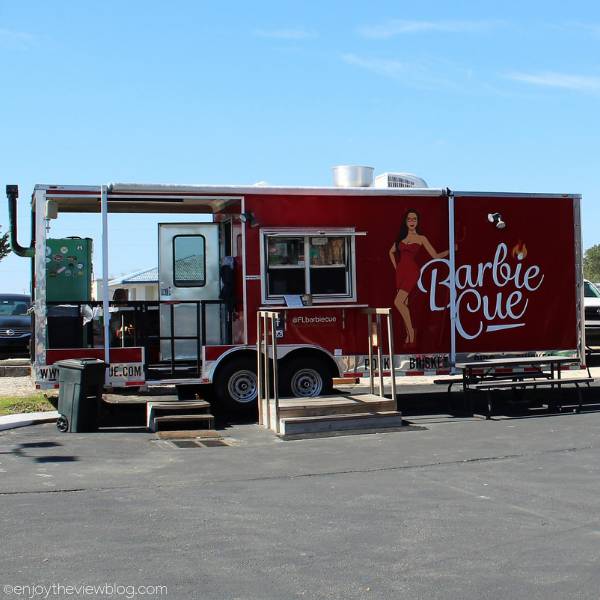 "red food truck that says ""BarbieCue"""