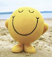 Deniz kenarında bir kumsalda gülümseyen mutlu bir emoji