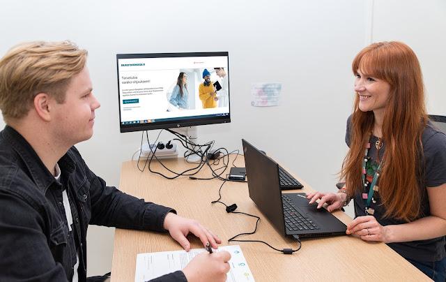 Kuvituskuva: Ohjaaja ja asiakas työpöydän ääressä