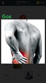 Мужчина рукой держится за бок, так как сильная боль заставляет