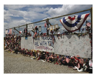 """Chain link fence with flowers, toys, flags inserted as tribute to passengers and crew of Flight 93. Two large pieces of plywood painted white have signatures all over them. A large sign in the center says """"Our Prayers Are With You."""""""