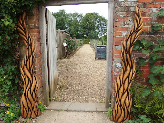 Anthony Rogers' timber sculptures frame the doorway into the Kitchen Garden at Avebury Manor