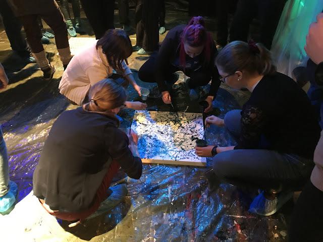 Henkilöitä maalaamassa lattialla olevalle kankaalle taideteosta