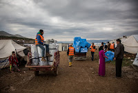 Aid workers delivering insulation to Syrian refugees in Iraq ahead of winter. (Credit: DFID/flickr) Click to Enlarge.