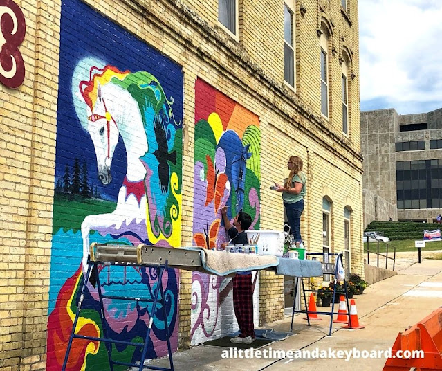 Whimsical Two Horses Mural being painted by artists Jessie Willyerd and Tim Cahill  in Janesville, Wisconsin.