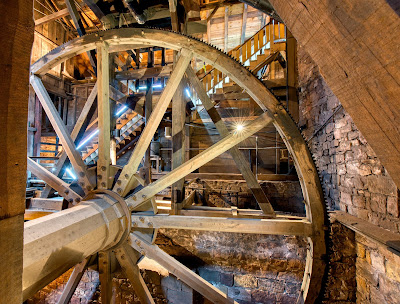 Large water wheel with gears, axle and surrounding stairs inside Cornwall Iron Furnace