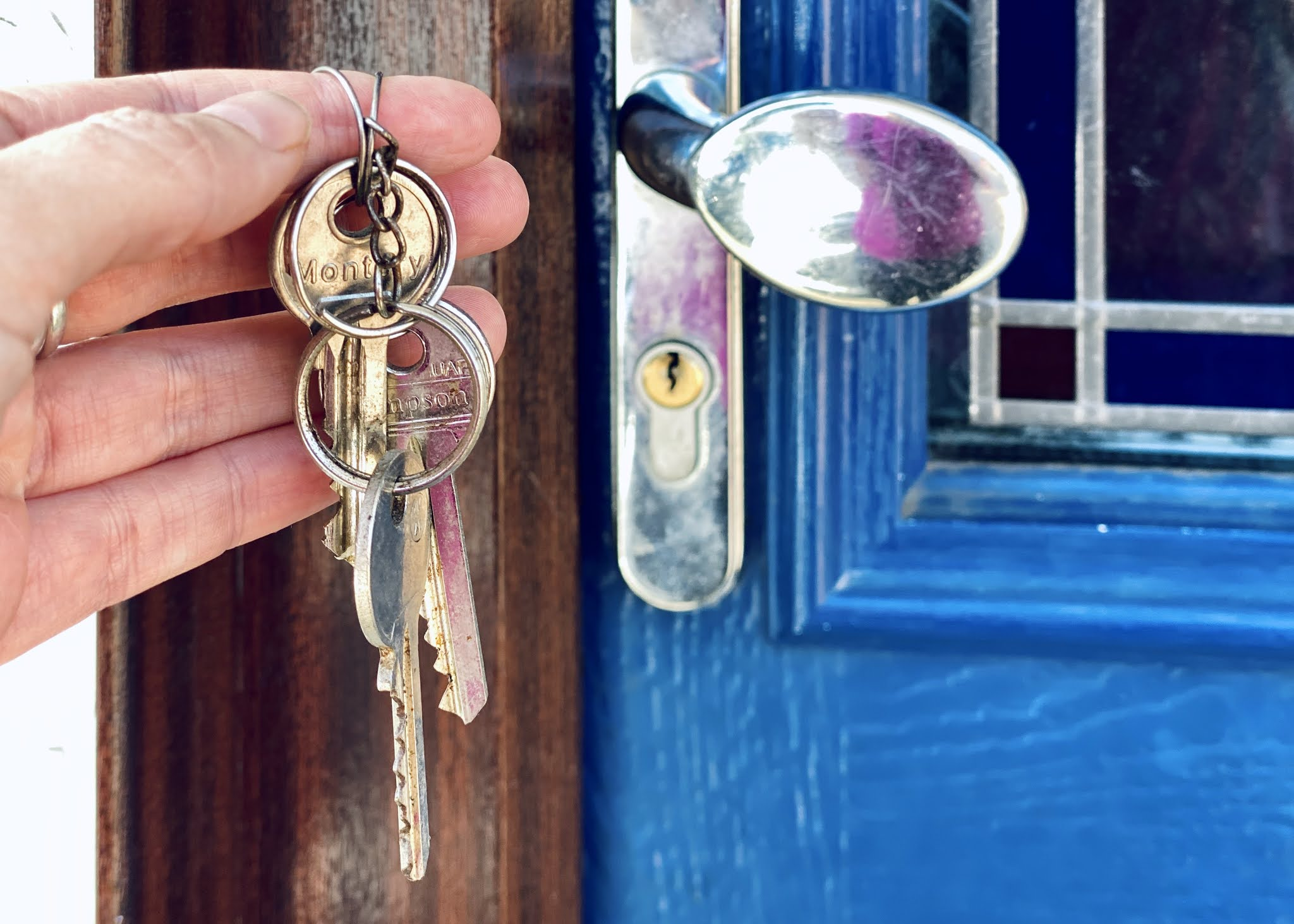 A set of keys outside a blue front door