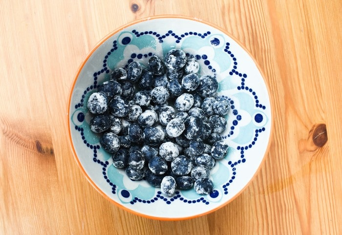 Blueberries coated in flour in a bowl