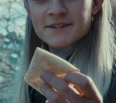 ID: lembas bread is held up with the bottom part of Legolas' face visible in the background.
