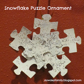 ornament made from puzzle pieces, paint and glitter to look like a snowflake