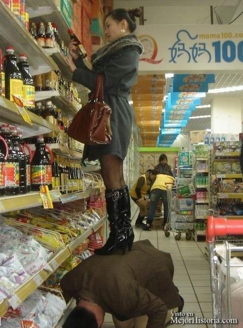 Hombre sirve de taburete para mujer en el supermercado. Ella lleva tacones que clava en su espalda. No parece importarle mucho.