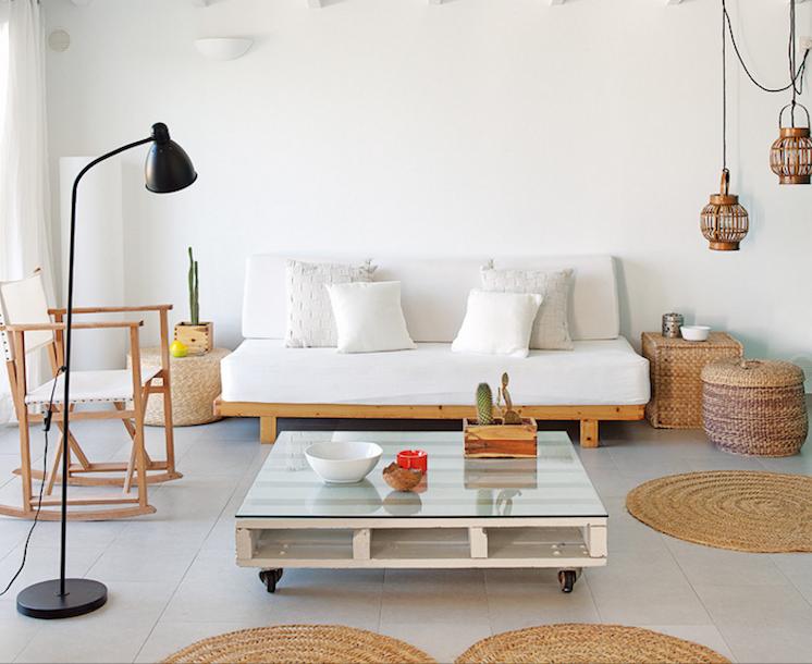 salón con sofá de madera, mesa de palets, alfombras de sisal