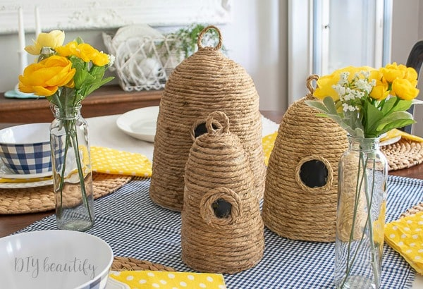 DIY bee skeps on dining table decorated with yellow and blue