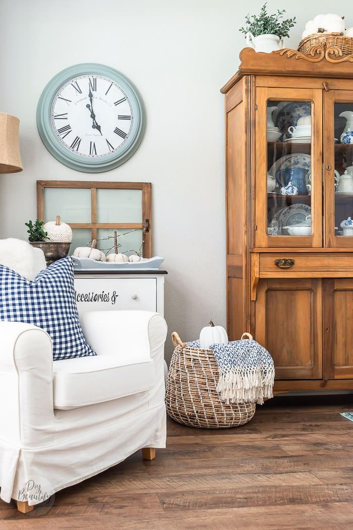 blue gingham pillow on neutral chair, neutral pumpkins, pine hutch