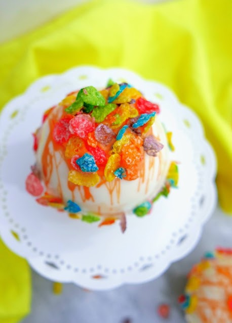 Fruity Pebbles Hot Cocoa Bombs with white plate and yellow background