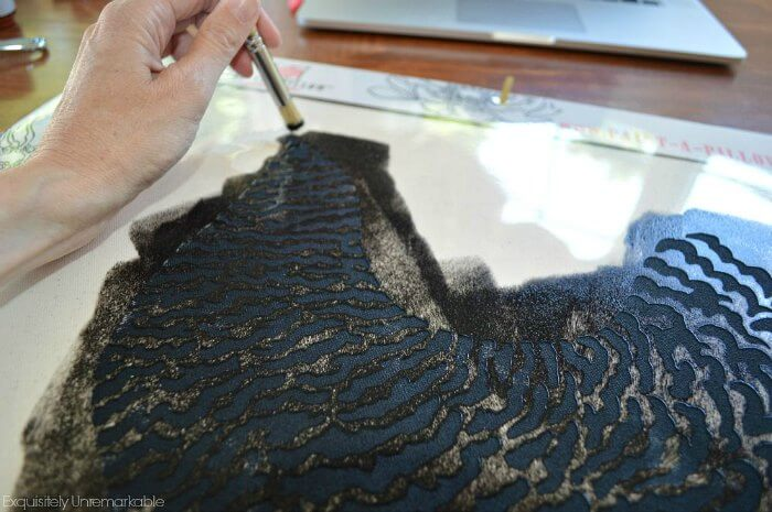 Using a paint brush to add paint to a pillow stencil