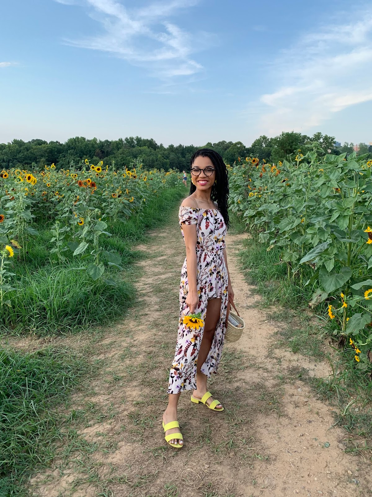 girl holding sunflower, sunflower photoshoot, sunflower field, flower jumpsuit, straw bag, summertime outfit, warby parker glasses, standing in sunflower field, yellow sandals, fashion blogger