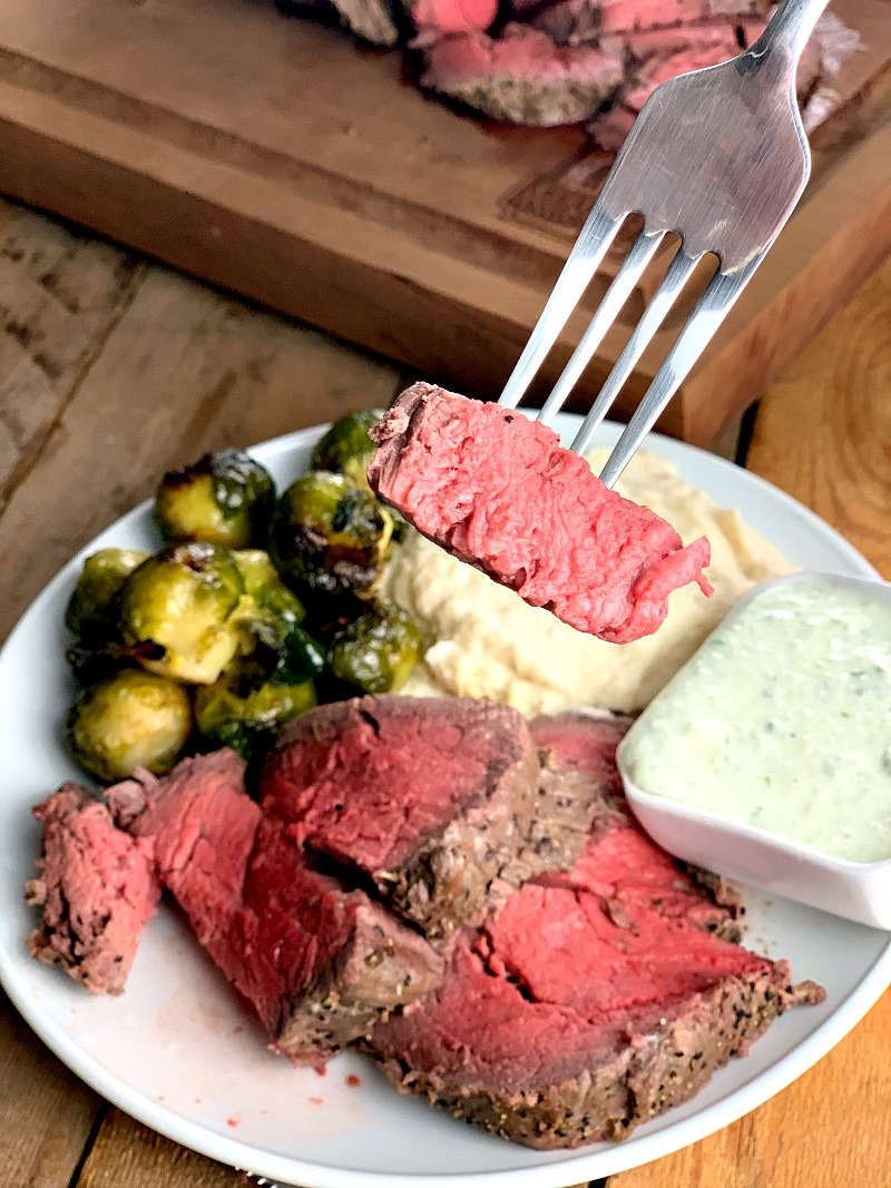 Photo of Greek-Style Beef Tenderloin with brussels sprouts and mashed cauliflower on a white plate.