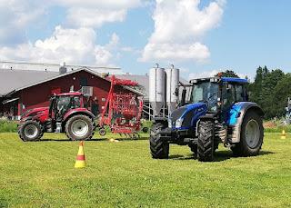 Kaksi traktoria nurmikentällä.