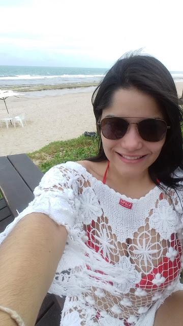 moça de oculos escuros tirando um selfie em uma praia