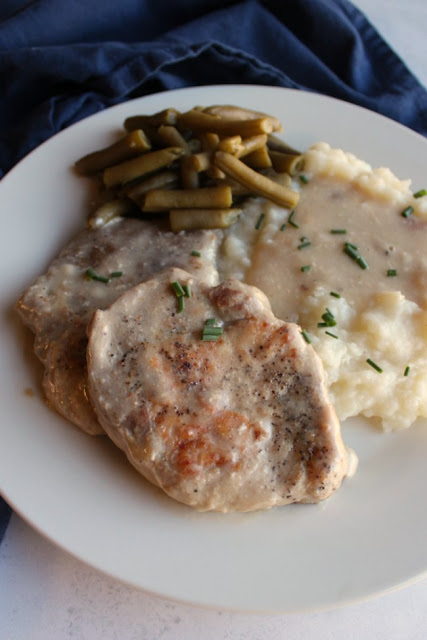 close up of tender pork chops and mushroom soup gravy served with mashed potatoes and green beans