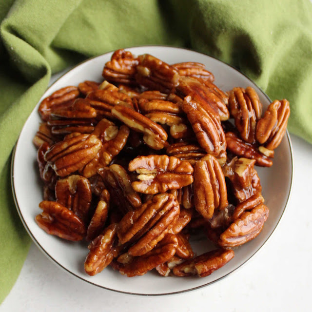 small bowl packed full with shiny honey coated pecans