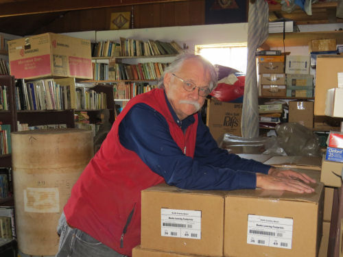 man leaning on a stack of cases of books