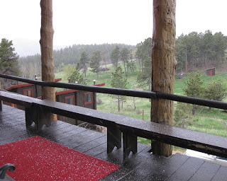 Pellets of hail on a red carpet and a wet deck at the Colorado Mountain Ranch