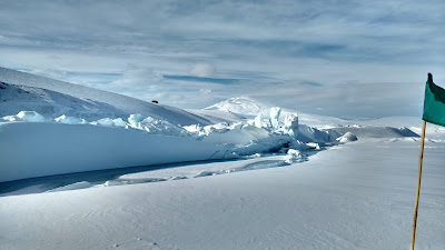 Green flag marks safe route to be taken on hikes in Antarctica, Pressure ridges making beautiful shape in Antarctica photo by Oindree Banerjee, used in blog how to phd, things to pack for antarctic expedition