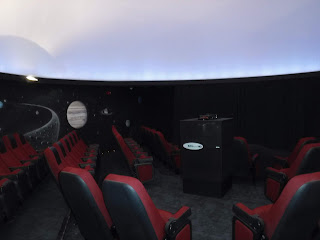 red and black theater seats int he Fred G. Dale Planetarium, a round room with black walls that have the moon and some stars painted on them. the bottom of a large white ceiling dome is visible above the black wall.