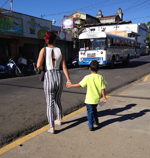 Woman holds child's hand waiting to cross Puriscal street