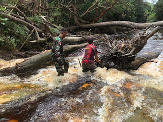 Cek Kondisi Wilayah,Babinsa Koramil 05/ Ketungau Hulu Bantu Warga Lewati Anak Sungai