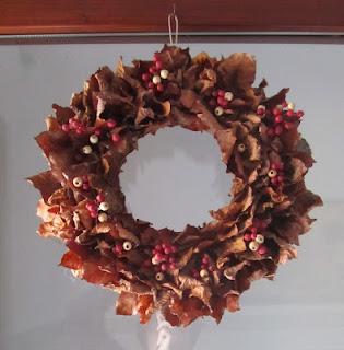 ghirlanda con foglie, cannella e bacche colorate
