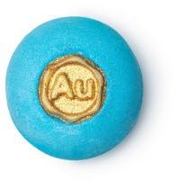 A blue spherical bath bomb with a gold circle in the middle with a star design on a bright background