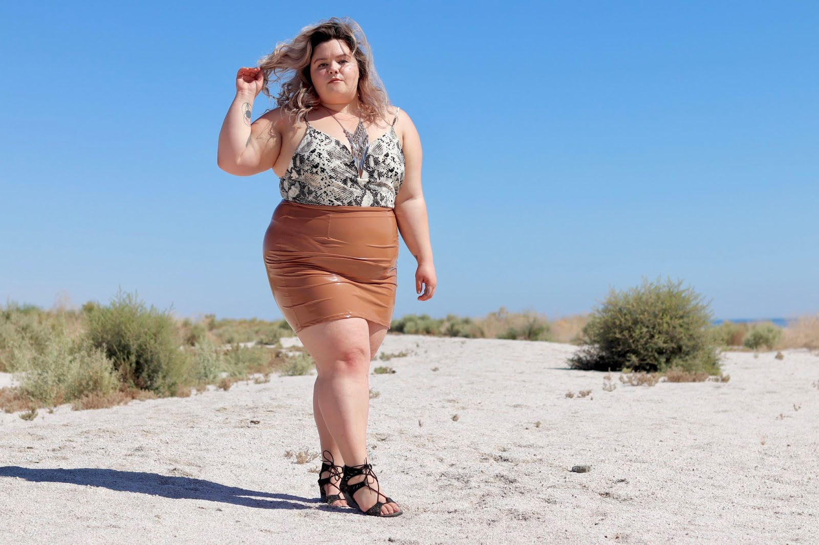 Chicago Plus Size Petite Fashion Blogger, YouTuber, and model Natalie Craig, of Natalie in the City, reviews Fashion Nova Curve's Slither My Way Bodysuit and Boot Camp Latex Skirt.