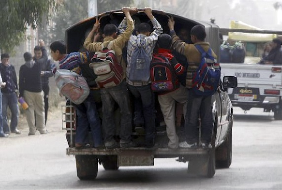 School kids in Cairo, Egypt hitching a ride at the back of a van
