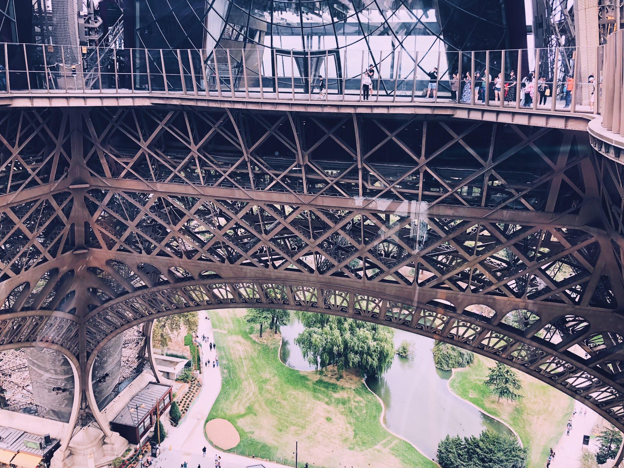 Foto gemaakt van op de Eiffeltoren met zicht op wat er zich onder de Eiffeltoren afspeelt.