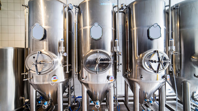 a row of silver tanks used for brewing