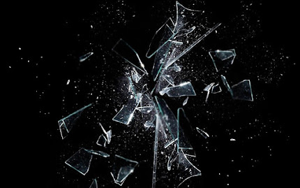 fragments of shattered glass explode against a dark background, like a field of stars