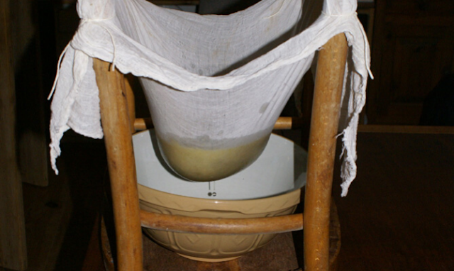 Straining jam with a muslin cloth and upside down chair